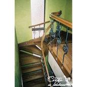 Деревянная лестница с декоративными коваными элементами
