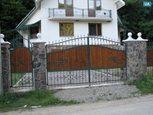 Деревянные ворота у дома с элементами ковки